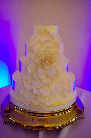 Four-Tier round cake, frosted smooth with vanilla French buttercream, decorated with ivory fondant...