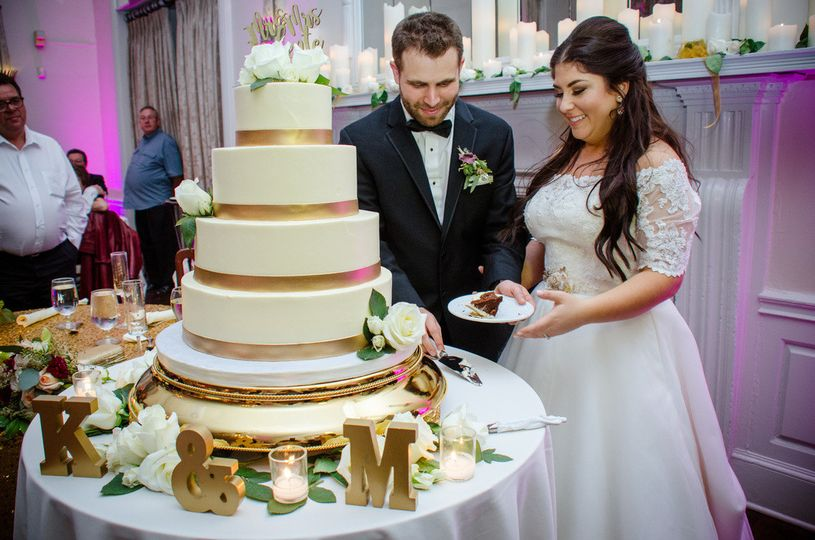 Tall wedding cake with gold ribbons