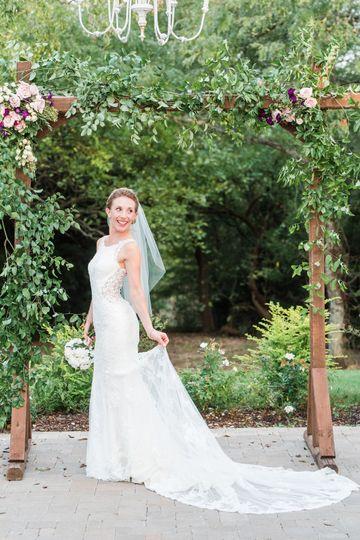 Bride smiling under arbor