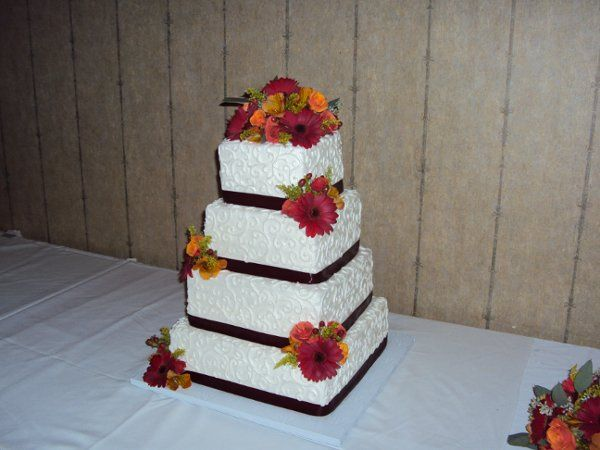A fall themed cake we decorated with red gerbera daisys alstromerial and miniture roses.