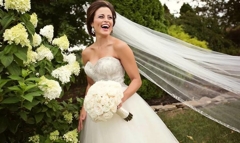 Bride smiles as her veil flows with the wind