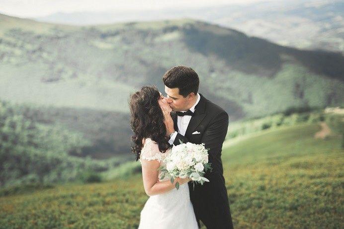 Newlyweds kiss on the mountain
