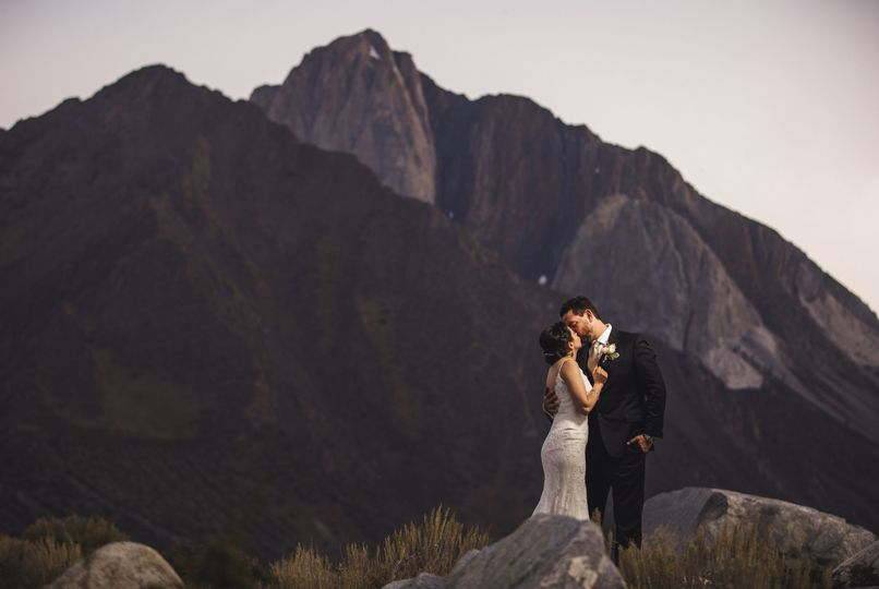 Newlyweds kissing with the mountains in the backdrop