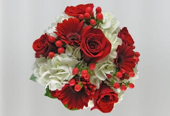 Crisp and clean bright red roses, gerber daisies and hypericum berries contrasted by white hydrangea...