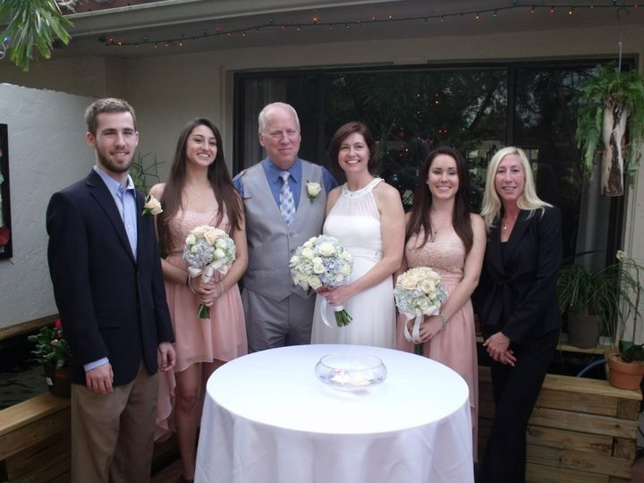 Newlyweds and their guests with the officiant