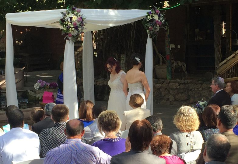 Two brides circle each other during a Jewish wedding at Boojum Tree Hidden Gardens.