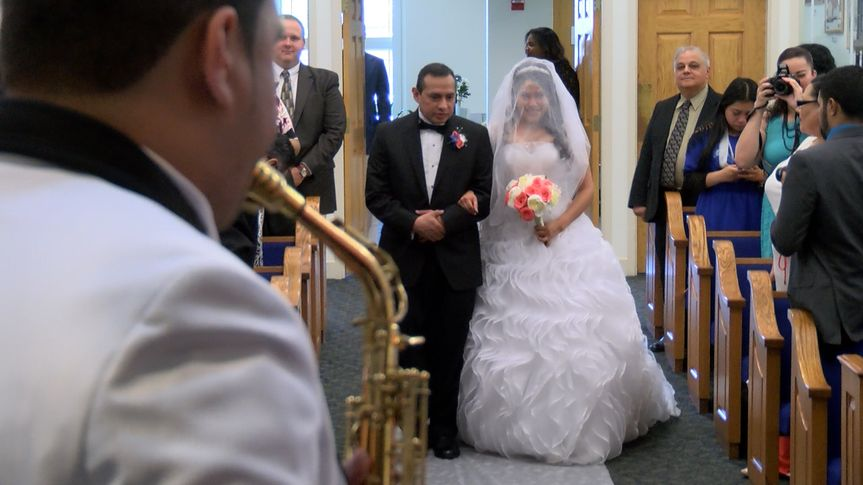 The groom playing the saxophone as his bride walks down the aisle