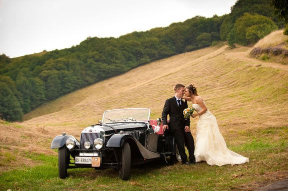 Newlyweds by a vintage coupe