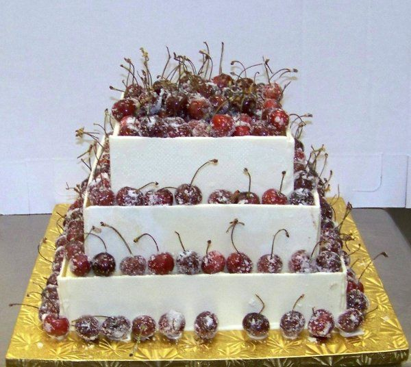 cheese cake with white chocolate sides and sugared cherries
