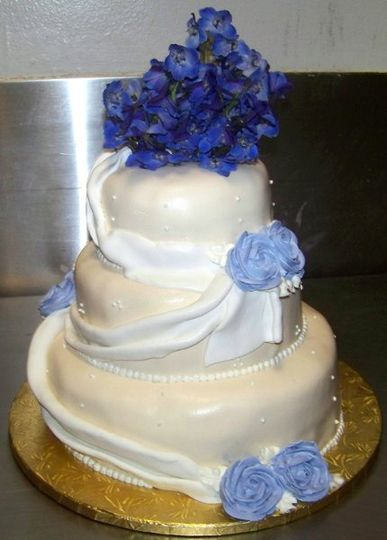 cake wrapped in fondant with blue icing roses and fresh blue flowers on top