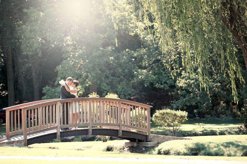 outdoor shot of bride and groom standing on bridge