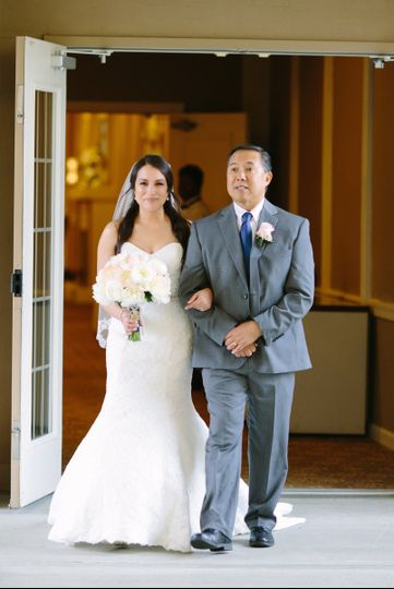 bride being walked onto patio with her father