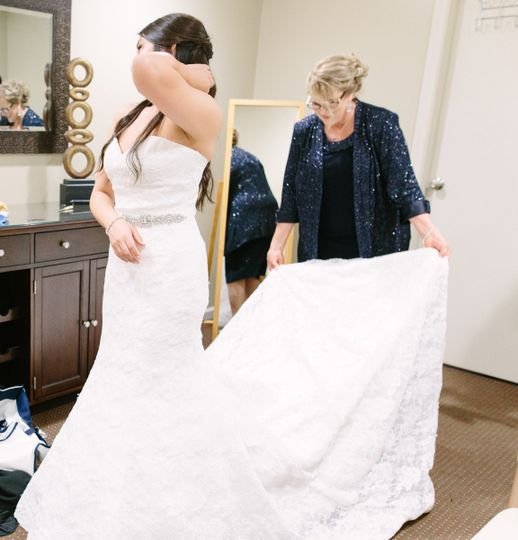 bride dressing in bridal room cropped