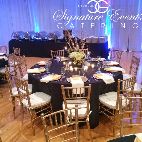 Elegant event space setup, featuring luxurious polished silver buffet warmers, real China plates,...