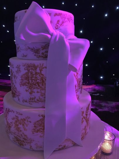 Wedding cake with gold bits and white ribbon