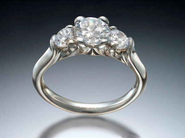 Three stone engagement ring with carved prongs