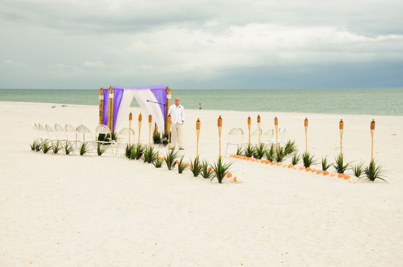 4 post bamboo canopy in exotic purple and white organza sails.Tiki sea grass and lion paws...