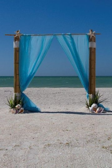 Wedding arbor with blue linen and shell decor