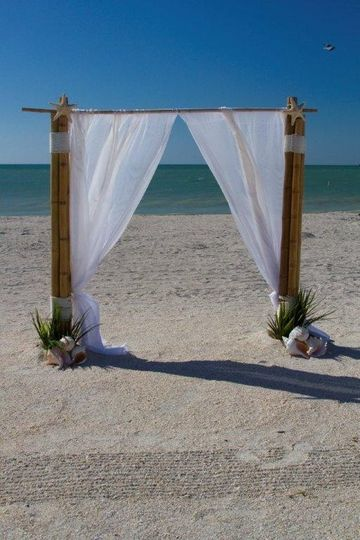 Wedding bamboo arch with white linen and shell decor