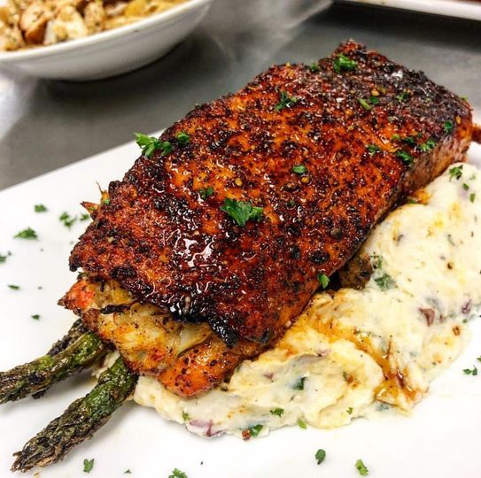 rosemary and asparagus stuffed wild caught salmon on a bed of roasted garlic mashed red potatoes