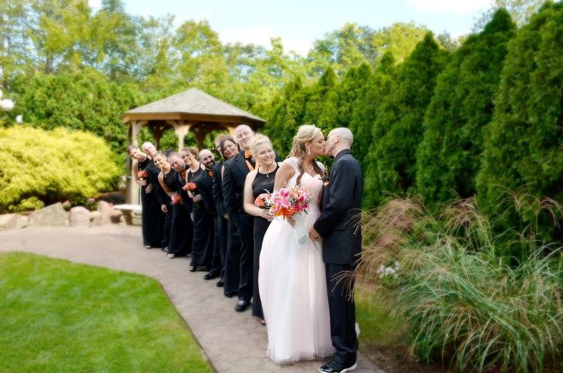 Couple kissing with the bridesmaids and groomsmen
