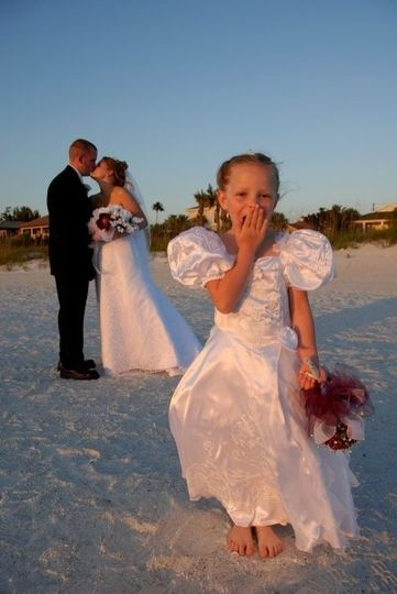 Newlyweds kissing behind the flower girl