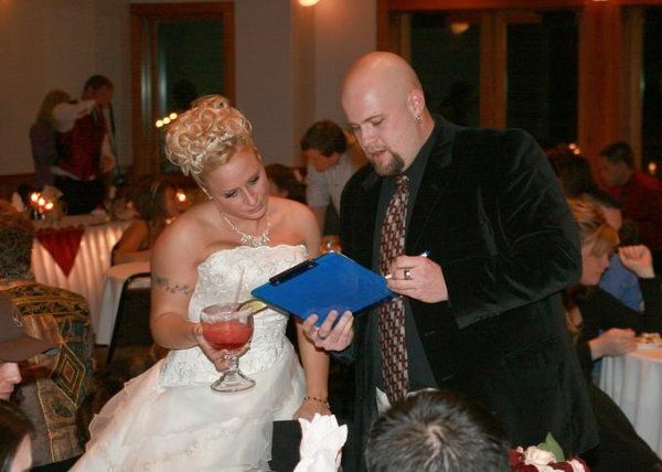 The company owner going over some details at a wedding reception at Upfront & Company.