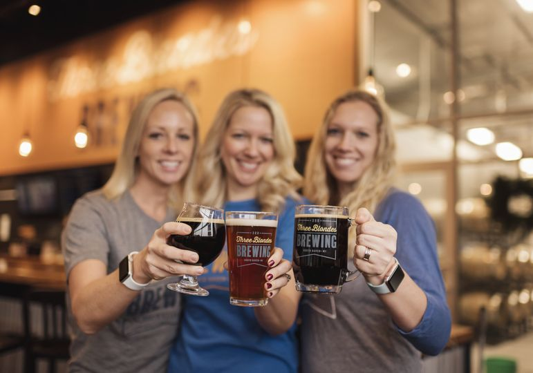 blondes cheersing in front of bar 51 1039325