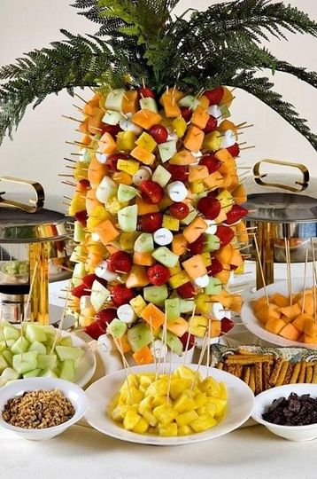 Assorted skewerd fruits on a pineapple tree served with melted dark and/or white chocolate and...