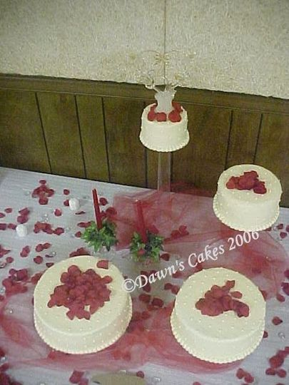 Chocolate and yellow cakes with buttercream icing and dots. Silk rose petals, tulle and candles to...