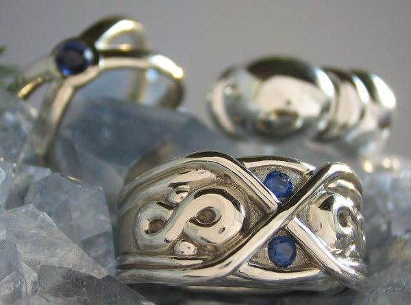 Pictured here is the Infinity Ring in 14K white gold with sapphires, the Sutton Ring in 14K white...