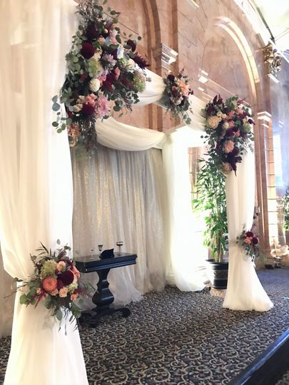 Chuppah of sheer fabric and Hayden flowers gathered