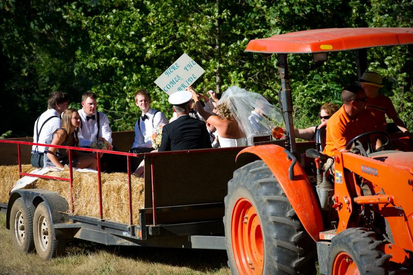 Newlyweds and their guests on a hay tractor