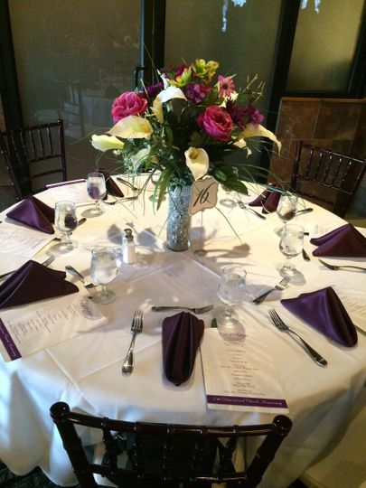 Banquet table setting with high centerpieces and colored purple linen napkins.