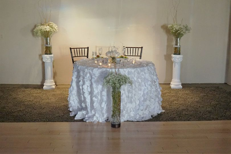 Beautiful and elegant royal white themed wedding. Sweetheart table draped with a petal table linen.