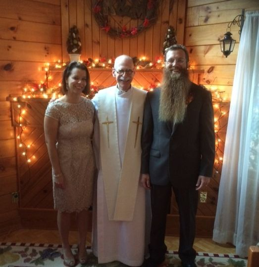 Smiling officiant with the newlyweds