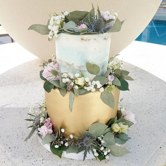 Blue watercolor and metallic gold buttercream wrapped in wild flowers