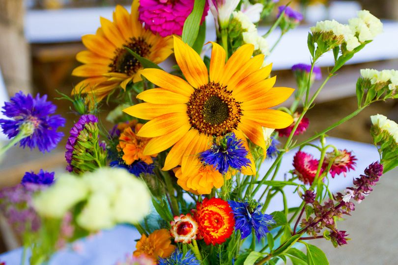Informal centerpiece with sunflowers and assorted wildflowers.