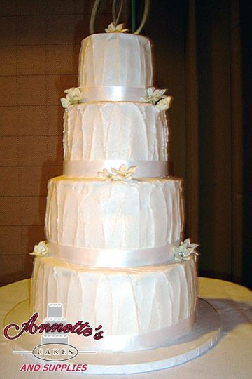 Beautiful 4 tier cake with ribbon work and flowers.