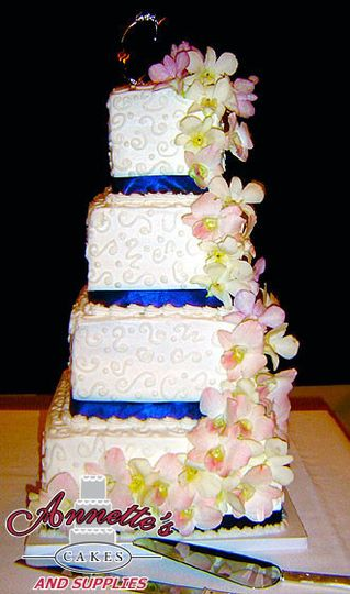 Colorful and glorious 4 tier buttercream cake with gorgeous azure colored ribbon work and flowers.