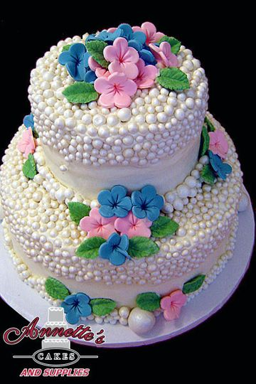 Neat 2 tier cake with superb dot work and varying handcrafted flowers!