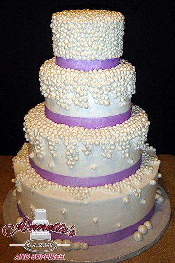 Opulent 4 tier cake with dazzling dotwork and beautiful lavender ribbon work!