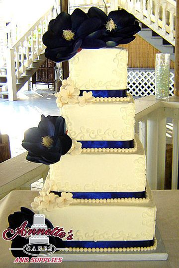 Perfect 4 tier quadratic cake with royal blue ribbon work and stunning handmade flowers!