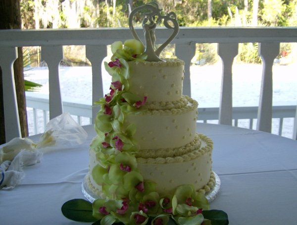 This elegant wedding cheesecake has a swiss dot design with breath taking lillies cascading down.