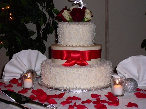 Christmas Eve Wedding at Castleton, top and bottom layer covered in coconut. Ribbon is Red Satin and...