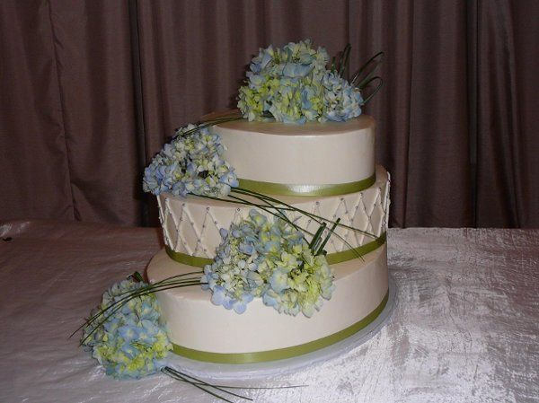 Wedding at Castleton.  Cake is oval, diamond pattern in middle has silver beads.  Flowers are blue...