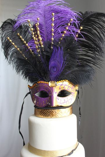 A Purple and Gold glittery and rhinestone masquerade mask sits on a black and gold (gold ribbon my...