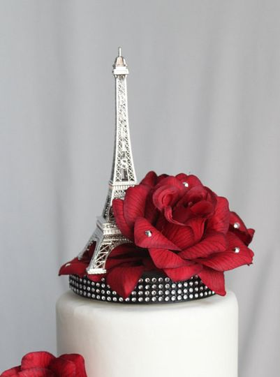 A bouquet of Red Roses sits on an elegant black silk base with a touch of silver surrounding a Paris...