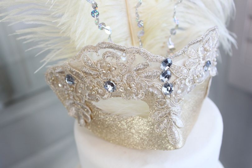 A gold and ivory mask with rhinestones is adorned with matching ivory ostrich feathers and a touch...