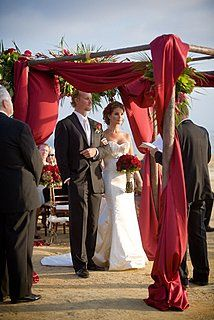 Arc de Belle's Sherwood Forest Canopy with red satin draping  Dark Wood Organic Inspired Wedding...